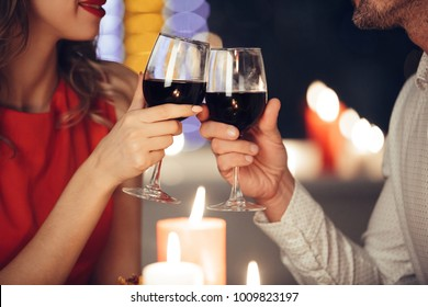 Close up of young couple holding glasses with red wine while have romantic dinner
