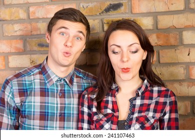 Close Up of Young Couple Puckering Lips and Standing in front of Brick Wall