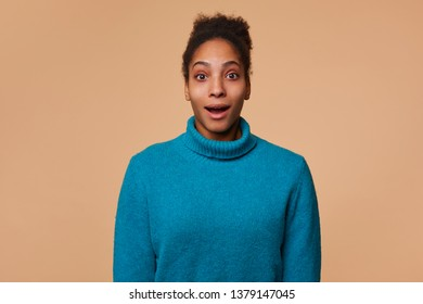 Close up of young dazed African American lady with curly dark hair, wearing a blue sweater, heard the incredible news. Wide open mouth and looking at the camer isolated over beige background.