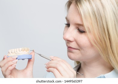 close up of young dental technician working on denture parts