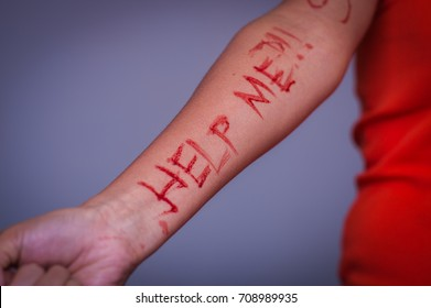 Close up of a young depressive woman, with her arm bleeding with the help word written in her arm with a knife, in a blurred background