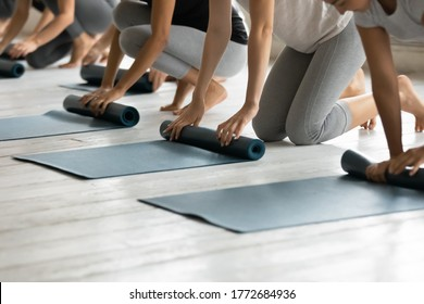 Close up young diverse barefoot people folding sport floor mats together, finishing yoga class lesson indoors, group of athletic friends unrolling rubber carpets, starting yoga workout at gym studio.