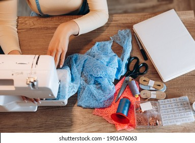 Close up young dressmaker woman with sewing machine. Creating online clothing design courses.