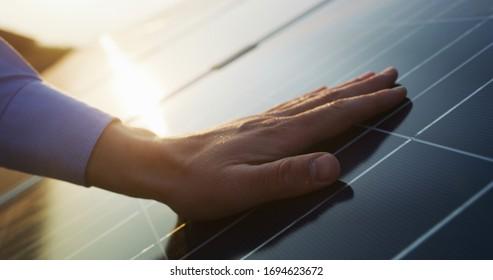 Nahaufnahme einer Hand eines jungen Ingenieurs ist die Überprüfung eines Betriebs von Sonne und Sauberkeit von Fotovoltaik-Solarpaneelen auf einem Sonnenuntergang. Konzept:erneuerbare Energien, Technologie, Strom, Dienstleistungen, umweltfreundliche Energie, Zukunft