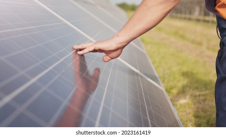 Close up of a young engineer hand is checking the operation of sun and cleanliness of photovoltaic solar panels on a sunset. Close-up of modern photovoltaic solar battery.