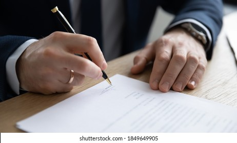 Close up young entrepreneur signing paper contract or business legal agreement, sitting at table. Focused male ceo executive manager putting signature on company financial or law document in office.