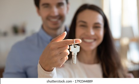Close up young excited couple showing keys in hands to camera. Happy homeowners celebrating moving in new apartment or last banking mortgage payment, feeling glad of purchasing property, real estate.