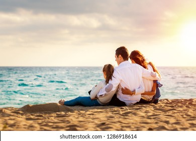 Close up of young family sitting together in late afternoon sun on beach.Foursome giving back looking at sea.