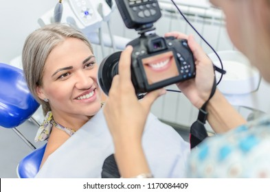 Close up of young female dentist taking picture of satisfied smilling female patient.