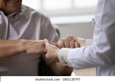 Close up young female doctor medical social worker gp holding wrinkled hands of elderly mature retired man, giving professional psychological help, first aid, supporting in stressful life situation.