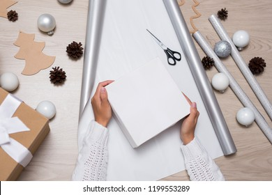 close up of young female hands packing Christmas gifts