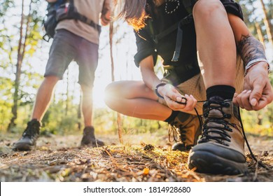 Close up of young female hiker tying shoelaces and getting ready for trekking in forest with man on background.