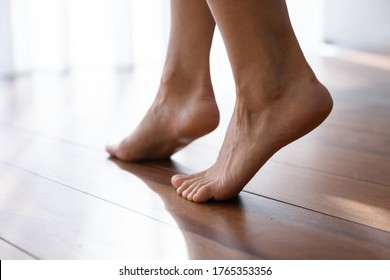 Close up of young female legs step barefoot on warm wooden floor in living room at home or hotel, woman girl walk with soft bare feet in apartment with underfloor electric heating