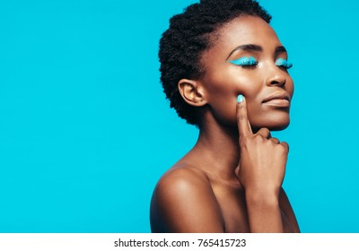 Close up of young female model with vibrant makeup against blue background. African young woman touching her perfect skin.