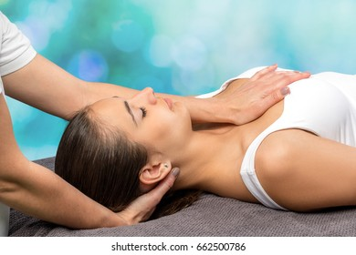 Close up of young female patient receiving physical therapy.Therapist manipulating back of head and chest against colorful background.