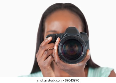 Close up of young female photographer against a white background
