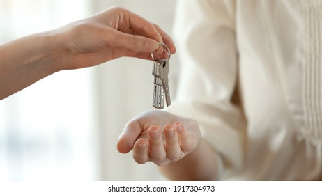 Close up young female real estate agent giving keys to happy buyer, congratulating with purchasing apartment. Millennial woman taking in leasing new house, accommodation tenancy rental service concept