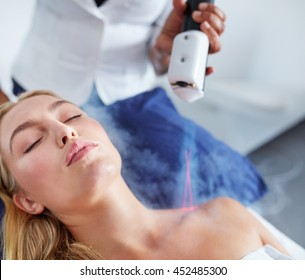 Close up of young female receiving local cryotherapy treatment to her shoulder. Nitrogen vapors applied to the neck and shoulders at spa.