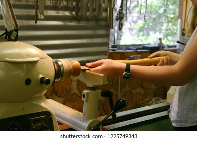 Close up of a young female woodworker turning a wooden bowl on a lathe in a woodworking studio