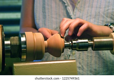 Close up of a young female woodworker's hands turning a wooden bowl on a lathe