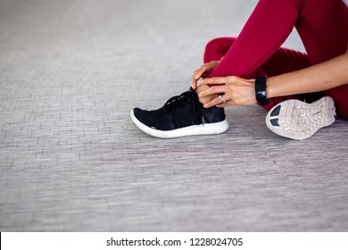 Close up of young fit and active female athlete suffering from ankle tendon ligament twisted and sprained from sports activity