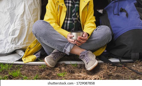 Close up of young girl hiker sits near a tent and drinking tea from thermos. Camping in the forest