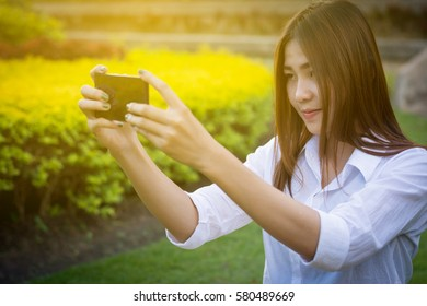 Close up young girl sitting on the lawn mobile phone.