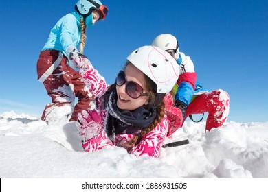 Gros plan de jeunes filles avec des vêtements colorés jouant dans la neige fraîche sur les pistes de ski et dans le ciel bleu en montagne