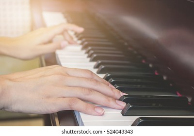 Close up of young girls hands, playing piano. vintage tone filter effected. selective focus.
