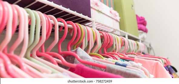 Close up of a young girl's neatly organized closet with bins and boxes.  Very shallow depth of field on the hangers.