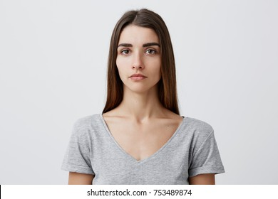 Close up of young handsome charming caucasian girl with long brown hair in gray t-shirt looking in camera with serious face expression. Woman getting photo for passport