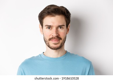 Close up of young handsome man with beard, smiling at camera with confidence, standing over white background