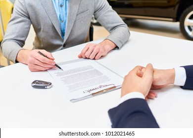 Close up of young handsome man reading purchase contract sitting at desk in dealership shop buying luxury car, copy space