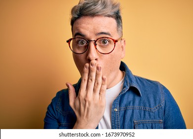 Close up of young handsome modern man wearing glasses and denim jacket over yellow background cover mouth with hand shocked with shame for mistake, expression of fear, scared in silence, secret