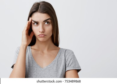 Close up of young handsome serious caucasian girl with long brown hair in stylish gray t-shirt touching forehead with hand, looking aside with tired face expression after long day in university