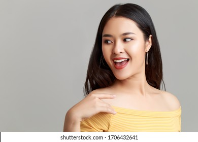 Close up young happy attractive Asian woman wearing yellow showing shoulder dress with sweet smile face isolated on grey background.