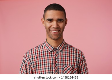 Close up of young happy attractive dark skinned guy in checkered shirt, looks at the camera with positive expression, broadly smiling and stands over pink background.