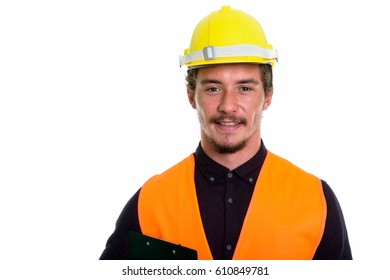 Close up of young happy man construction worker smiling while holding clipboard isolated against white background