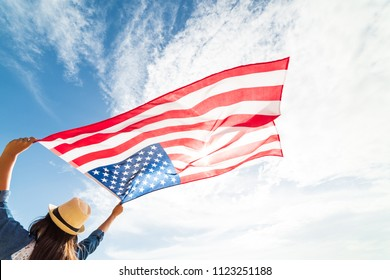 Close up young happy woman holding United States of America flag and running, jumping carefree with open arms with blue sky. USA Independence day, 4 July.