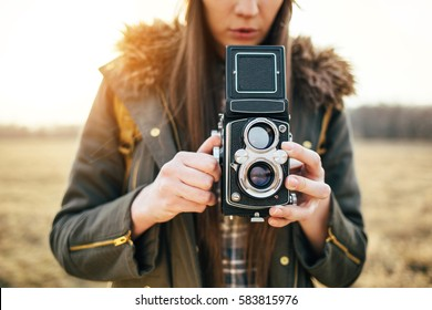 Close up of young hipster girl with vintage camera. Female photographer with retro camera