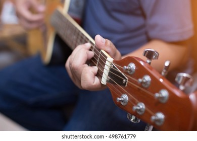 Close up of young hipster man practiced guitar in the park,happy and enjoy playing guitar.