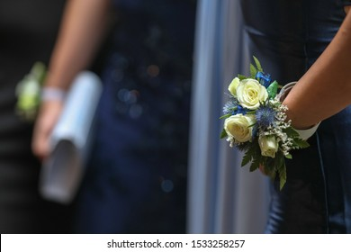 A close up of young laddies in blue gowns with corsages getting ready for high school prom.