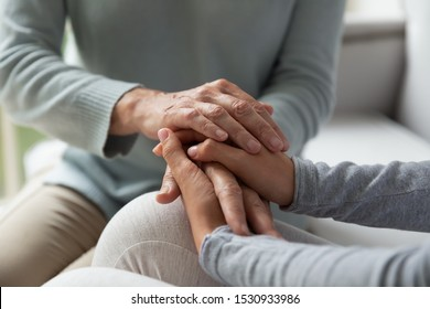 Close up young lady and middle aged woman connecting hands, holding sincere conversation at home. Caring grown up daughter and mature mother demonstrating love, care and support, trust symbol.