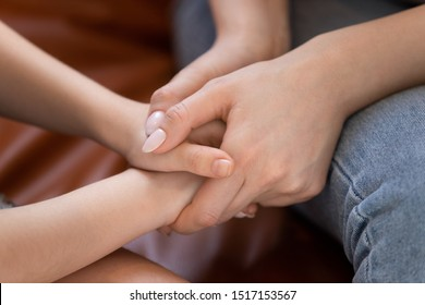 Close up young loving carrying mother holding hands of little kid boy or girl, supporting comforting school child, suffering from bullying, showing love care, reconciling after quarrel, tender moment.