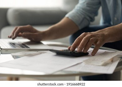 Close up of young male accountant hands make audit of expenses calculate charges based on paper documents. Cropped shot of man bookkeeper work with bills pay fees taxes online using web app on laptop