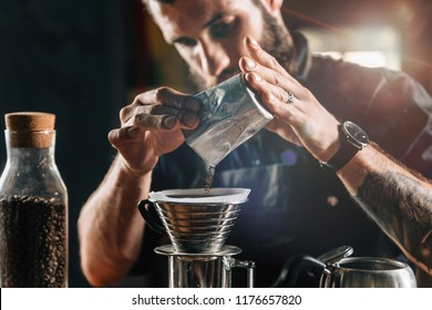 Close up of a young male barista pouring coffee into Kalita Wave Dripper to brew coffee and measure it on digital scale in coffee shop. Barista wearing dark uniform.