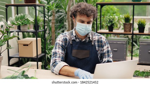 Close up of young male entrepreneur in flower shop sitting at table and typing on laptop. Portrait of handsome Caucasian joyful man greenhouse worker in mask browsing on computer. Job concept