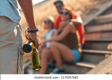 Close up of young male hand carrying beer to friends.