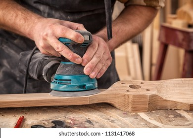 Close up of an young man builder carpenter equals polishes wooden board with a  random orbit sander  in the workshop