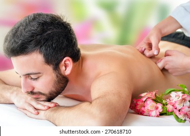 Close up of young man enjoying back massage. Young man laying face down and therapist hands massaging lower back.